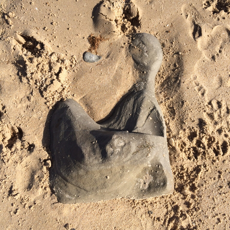 rock in sand reminiscent of a Henry Moore sculpture